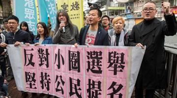 DIBURU: Wong (tiga kanan) menyertai para penunjuk perasaan yang berarak tanda protes ke lokasi pilihan raya ketua eksekutif di Hong Kong, kelmarin. — Gambar AFP