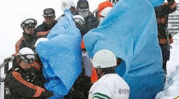 TRAGIK: Pekerja penyelamat mengusung mangsa dari tempat kejadian berhampiran pusat peranginan ski di bandar Nasu, utara Tokyo dalam gambar rakaman Kyodo semalam. — Gambar Reuters