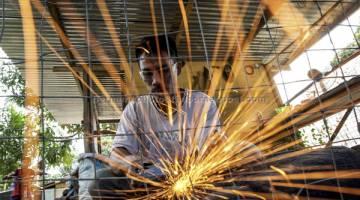 TELITI: Haddy Piris, 35, sedang menggunakan mesin gerinda untuk meratakan dan menajamkan mata parang selepas proses menempa (dibakar dan diketuk berulang kali) di bengkelnya di Kampung Kipaliu, Kinaratuan, Ranau, Sabah.  — Gambar Bernama