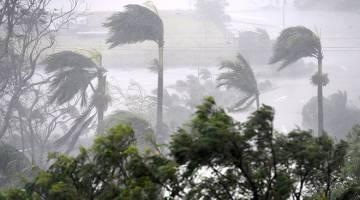 MENGGERUNKAN: Angin kencang dan hujan lebat membadai Pantai Airlie selatan bandar utara Townsville, semalam. — Gambar Reuters