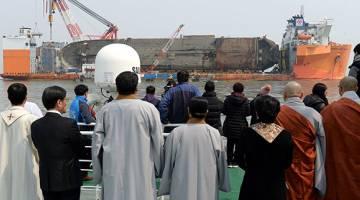 BERHARAP: Orang ramai dan ahli keluarga mangsa tragedi feri menyaksikan operasi menyelamat bangkai kapal luar pantai pulau selatan Jindo, kelmarin. — Gambar AFP