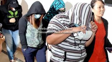 DIBAWA KELUAR: Kesemua tertuduh meninggalkan kamar mahkamah dengan ikat jamin selepas mengaku tidak bersalah atas pertuduhan rasuah di Kuching, semalam.