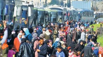 MALANG: Penduduk yang dipindahkan dari dua bandar Kafraya dan Fuaa berhimpun berdekatan bas-bas yang ditangguhkan perjalanannya di Rashidin, wilayah Aleppo kelmarin manakala gambar kanan menunjukkan asap hitam berkepul susulan serangan bom van menyasari bas-bas itu. — Gambar Reuters/AFP