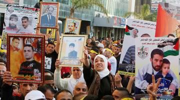 AMAT DIRINDUI: Penduduk Palestin menunjukkan gambar ahli keluarga mereka yang masih ditahan di penjara rejim Israel semasa perarakan Hari Tahanan Palestin di Nablus, Tebing Barat kelmarin. — Gambar Reuters
