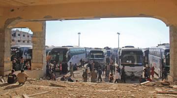 HIDUP MESTI DITERUSKAN: Orang awam dan pemberontak dari bandar Fuaa dan Kafraya tiba dengan bas di pinggir Rashidin luar Aleppo semalam. — Gambar AFP