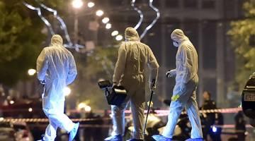 CARI BUKTI: Pegawai forensik memeriksa bukti selepas serangan bom merosakkan cawangan bank Greek, Eurobank, di tengah Athens, kelmarin. — Gambar AFP