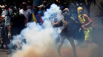 HURU-HARA: Penunjuk perasaan bertempur dengan polis rusuhan ketika menyertai 'perarakan terbesar' menentang pemerintahan Maduro di Caracas, Venezuela, kelmarin. — Gambar Reuters