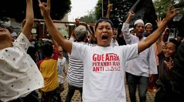 BERSORAK GEMBIRA: Penyokong calon Gabenor Jakarta Anies Baswedan bersorak gembira ketika Baswedan mendahului dalam kiraan undi di pusat mengundi Petamburan di Jakarta, Indonesia kelmarin. — Gambar Reuters