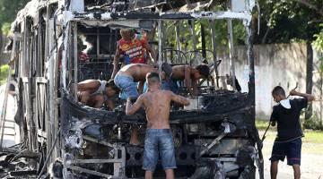 AMBIL KESEMPATAN: Orang ramai dilihat menanggalkan rangka bas yang rentung di Fortaleza, Brazil kelmarin. — Gambar Reuters