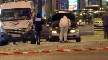MEMERIKSA BUKTI: Imej pegun daripada rakaman video menunjukkan penyiasat polis memeriksa kereta digunakan penyerang di Champs Elysees Avenue selepas seorang anggota polis terbunuh dan dua lagi cedera dalam insiden tembakan di Paris, Perancis kelmarin. — Gambar Reuters