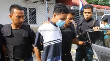 MEMBUNUH: Amirul (dua kiri) dihadapkan ke Mahkamah Majistret semalam atas pertuduhan membunuh bapa kandungnya di rumahnya di Padang Besar, Kangar. — Gambar Bernama
