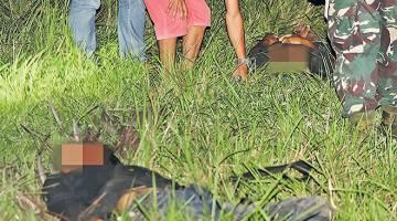 MAUT: Gambar yang dirakam lewat kelmarin menunjukkan askar Filipina (kanan) dan orang awam melihat dua daripada empat mayat lelaki bersenjata yang terbunuh di bandar Clarin, wilayah Bohol. — Gambar AFP