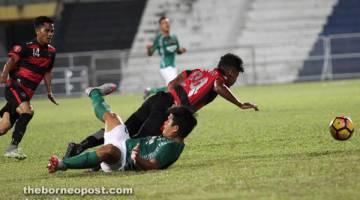 KAWAL: Penyerang Kuching FA, Sufizal Ismail (hijau) mengasak pertahanan Terengganu City FC, Muhd Zulhairi Ismail pada perlawanan Piala FAM kelmarin.