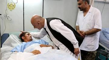 TURUN PADANG: Ghani bertanya khabar seorang mangsa yang cedera dalam serangan Taliban semasa melawat Mazar-i-Sharif Sabtu lalu. — Gambar Reuters