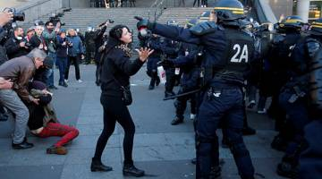 RUSUHAN: Penunjuk perasaan cuba berunding dengan polis antirusuhan semasa pertempuran di Paris, kelmarin. — Gambar Reuters