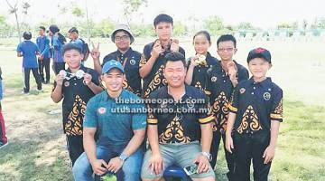 TERBAIK: Pasukan pemanah dari Sarawak (berdiri di belakang) gembira menunjukkan medal yang dimenangi bersama Ricky (duduk kanan) di Perlis.