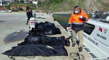 NASIB TRAGIK: Anggota penyelamat giat mengeluarkan mayat mangsa yang telah dimasukkan ke dalam beg mayat di atas dermaga bersebelahan kapal pengawal pantai Turki, di kampung pelabuhan Aegean Babakale di wilayah Canakkale kelmarin. — Gambar Reuters