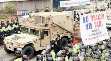 DICURIGAI: Sebuah kenderaan tentera AS yang membawa sebahagian sistem THAAD tiba di Seongju, semalam di mana tunjuk perasaan membantahnya dikawal ketat polis. — Gambar Reuters