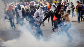 HURU-HARA: Penyokong pembangkang bertempur dengan pasukan keselamatan semasa perhimpunan anti-Maduro di Caracas, Venezuela kelmarin. — Gambar Reuters