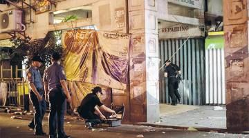 SIASATAN: Pegawai polis menjalankan siasatan di lokasi letupan di Quiapo, Manila kelmarin selepas bom paip buatan sendiri meletup. — Gambar AFP