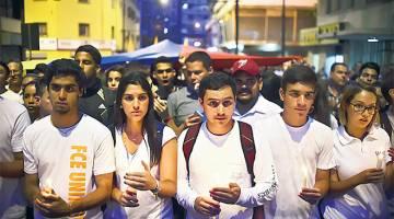 BERI PENGHORMATAN: Pelajar Venezuela menyertai perarakan yang memberi penghormatan kepada rakan sekolah mereka Juan Pablo Pernalete terbunuh 26 April lalu akibat impak grenade gas semasa protes mennentang Presiden Nicolas Maduro- di Caracas, kelmarin. — Gambar AFP