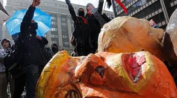BINGIT: Penunjuk perasaan bersorak selepas merobek kepala patung Trump semasa demonstrasi Hari Buruh di Chicago, kelmarin. — Gambar AFP