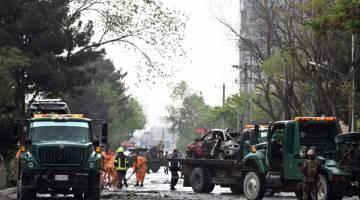 BERKECAI: Kakitangan keselamatan menjalankan siasatan di tempat kejadian yang menyasari konvoi tentera asing dekat kedutaan AS di Kabul, semalam. — Gambar AFP