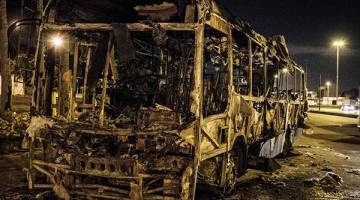 MELAMPAU: Sebuah bas hangus dibakar anggota kumpulan dadah di Avenida Brasil di Rio de Janeiro, kelmarin. — Gambar AFP