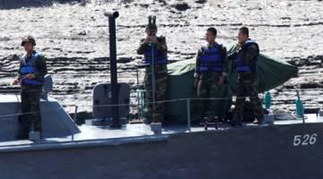 INTAI: Tentera Korea Utara meneropong dari kapal di Sungai Yau berhampiran bandar sempadan Dandong di China pada Selasa lalu. — Gambar Reuters
