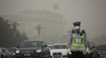 SABUT KELABU: Dewan Besar Rakyat hampir tidak kelihatan ketika ribut debu melanda Beijing, China semalam. — Gambar Reuters