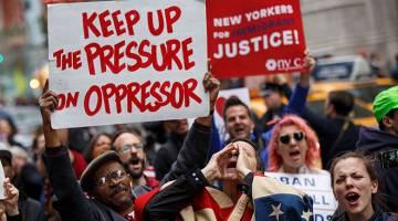 SUARA RAKYAT: Pembantah melaungkan slogan anti-Trump ketika menyertai perarakan di New York kelmarin. — Gambar AFP