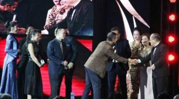 Uggah (kanan) menyampaikan trofi anugerah kepada Bade serta krew yang menjayakan Filem Kanang Anak Langkau