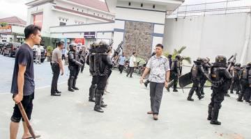 KECOH: Seorang penduduk kampung (kiri) yang tinggal berhampiran dan anggota polis antirusuhan bersenjatakan raifal berkawal di depan kompleks Penjara Sialang Bungkuk dalam gambar rakaman Antara Foto kelmarin. — Gambar Reuters