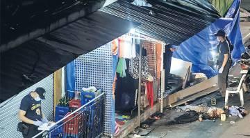 MENGGEMPARKAN: Mayat seorang mangsa bergelimpangan di tempat kejadian ketika para pegawai polis membuat siasatan di Quiapo, Manila kelmarin. — Gambar AFP