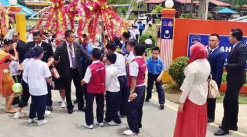 DIHARGAI: Murid-murid SK Tatau bersalaman dengan John yang diiringi Janudin.