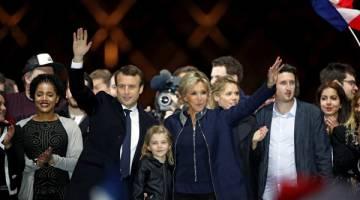 MENANG: Macron meraikan kejayaannya di atas pentas dengan diiringi isterinya Brigitte Trogneux di hadapan Piramid Muzium Louvre di Paris, kelmarin. — Gambar AFP