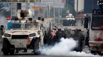 KECOH: Pegawai polis antirusuhan bertempur dengan penyokong pembangkang semasa rali anti-Maduro di Caracas, kelmarin. — Gambar Reuters