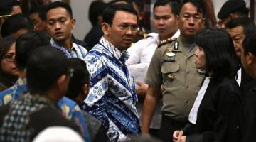 TENANG: Purnama (tengah) bercakap dengan pasukan peguam belanya selepas hukuman dijatuhkan hakim dalam perbicaraan di Jakarta, semalam. — Gambar Reuters