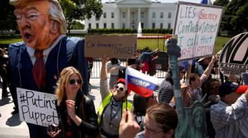 TUNTUT SIASATAN: Penunjuk perasaan berhimpun untuk membantah tindakan Trump memecat pengarah FBI di luar pekarangan Rumah Putih di Washington, kelmarin. — Gambar Reuters