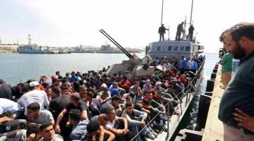 HASIL PINTASAN: Ratusan pendatang, yang bot kayu mereka dipintas oleh pasukan pengawal pantai Libya di Laut Mediterranean, tiba di pangkalan tentera laut di Tripoli kelmarin. — Gambar AFP