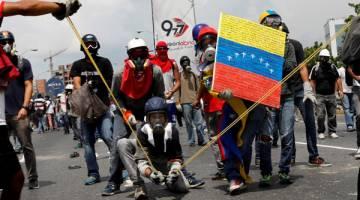 'BOM NAJIS': Penunjuk perasaan menggunakan lastik besar untuk membaling 'koktel Poopootov' – najis yang disimpan dalam botol kaca kecil, ketika menyertai perhimpunan menentang Maduro di Caracas, Venezuela, kelmarin. — Gambar Reuters