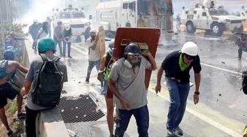 HURU-HARA: Penunjuk perasaan bertempur dengan pasukan keselamatan ketika perhimpunan menentang Maduro di Caracas, Venezuela pada 10 Mei. — Gambar Reuters