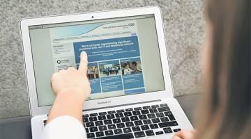 DISERANG: Seorang wanita menunjukkan laman sesawang NHS: Hertfordshire Timur dan Utara yang memaklumkan kepada para pengguna mereka mengenai masalah dalam rangkaiannya, di London kelmarin. — Gambar AFP