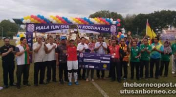 JULANG: Ketua pasukan Sarawak menjulang piala kemenangan Piala Tun Sharifah Rodziah edisi ke-30 di Stadium Miri.