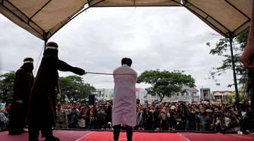 HUKUMAN DUNIA: Salah seorang pesalah dalam kes seks gay disebat dengan rotan di khalayak ramai di pekarangan masjid di Banda Aceh, Aceh semalam. — Gambar Reuters