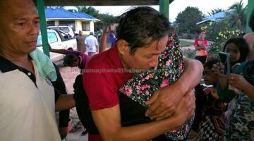 HIBA: Mohd Zulkifli memeluk anak bongsunya Syakilah sebaik tiba di kampung halamannya kelmarin. — Gambar Bernama