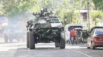 KETEGASAN DILAKSANAKAN: Sebuah kereta kebal membawa anggota tentera memasuki lebuh raya utama bandar Pantar, Lanao Del Norte dalam perjalanan untuk mengukuhkan keselamatan di Marawi, semalam. — Gambar Reuters