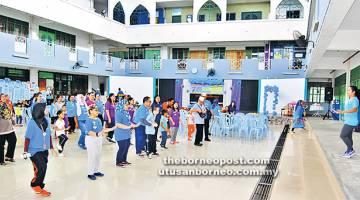 SENAMAN: Sebahagian kanak-kanak autisme dan penjaga mereka menyertai acara senaman sebelum upacara perasmian bermula pada paginya.