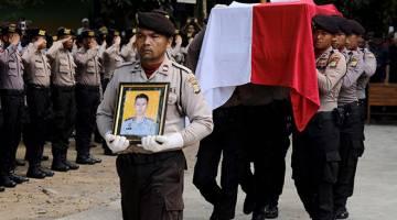 PENGHORMATAN: Polis Indonesia mengusung keranda rakan            sekerja Imam Gilang Adinata yang terkorban dalam letupan bom      di terminal bas Kampung Melayu di Jakarta, kelmarin. — Gambar Reuters