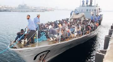 DISELAMAT: Para pendatang tiba dengan bot di sebuah pangkalan tentera selepas diselamatkan oleh pegawai pengawal pantai Libya di Tripoli, Libya kelmarin. — Gambar Reuters